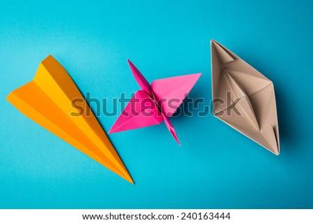row of colored paper origami plane crane, boat - stock photo