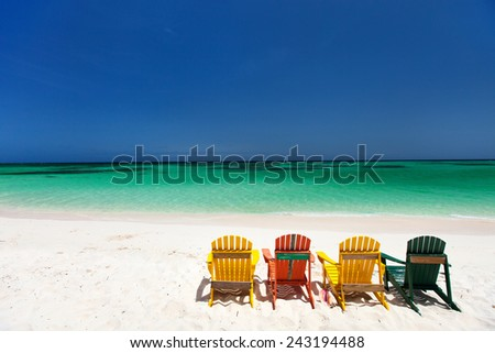 Row of colorful adirondack wooden chairs at tropical white sand beach in Caribbean - stock photo