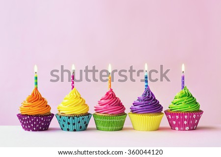 Row of colorful birthday cupcakes