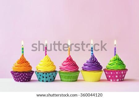 Row of colorful birthday cupcakes - stock photo