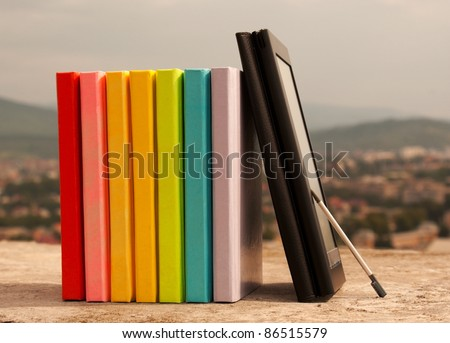 Row of colorful books with electronic book reader - stock photo