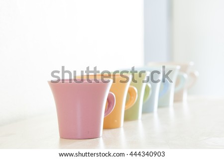 Row of colorful coffee cups on clear background.