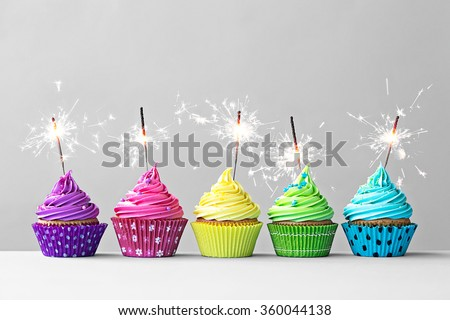 Row of colorful cupcakes with sparklers - stock photo