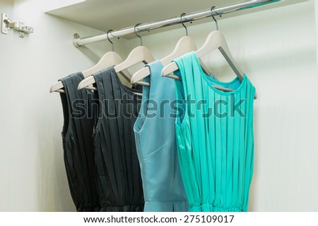 row of colorful dress hanging on coat hanger in white wardrobe