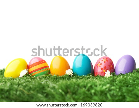 Row of colorful Easter eggs in green grass - stock photo