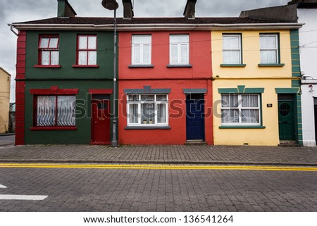 Row of colorful green, red, and yellow Irish houses in Limerick, Ireland line the cobblestone street - stock photo