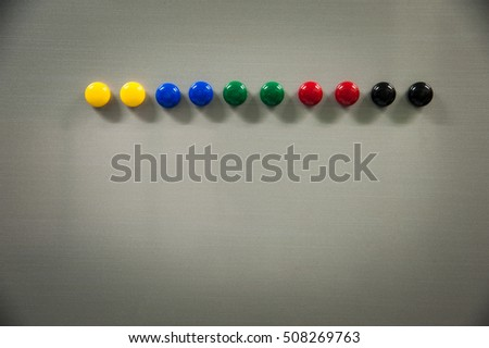 Row of colorful magnet on refrigerator door