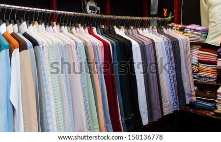 row of colorful  shirts hanging in shop for sale - stock photo