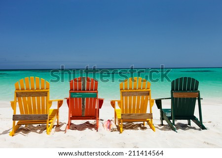 Row of colorful wooden chairs at tropical white sand beach in Caribbean - stock photo