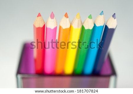 Row of colorful wooden crayons in glaas jar, macro with shallow dof. Selective focus. - stock photo