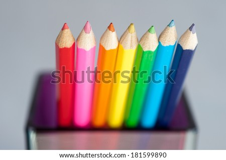 Row of colorful wooden crayons in glaas jar on grey background, macro with shallow dof. Selective focus. - stock photo