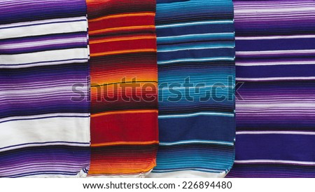 Row of colorful woven blankets for sale at Mexican market