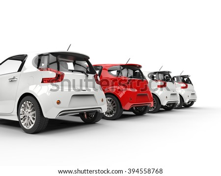 Row of compact cars - red stands out - back perspective view - stock photo
