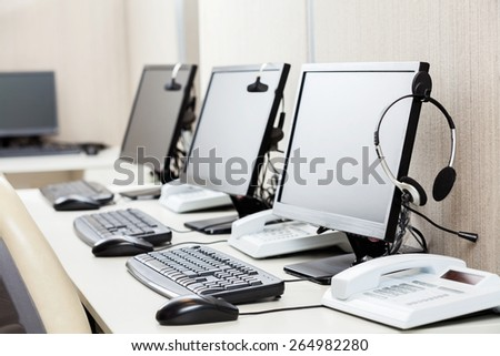 Row of computers with headphones on desk at call center - stock photo