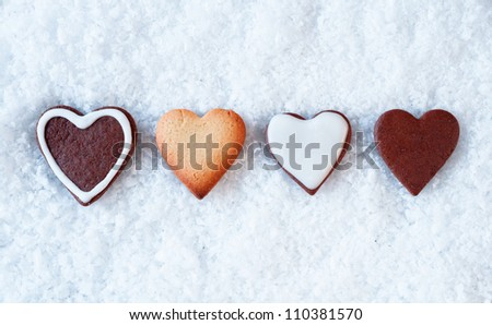 Row of crisp baked gingerbread hearts on a snowy background with copyspace above and below for Christmas greetings - stock photo