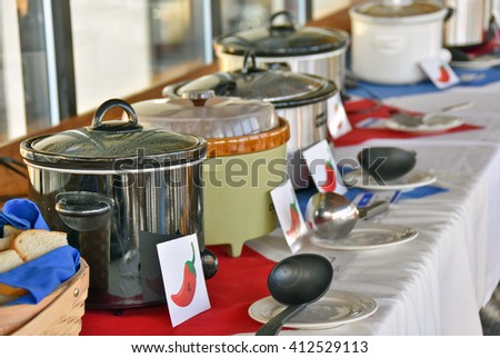 row of crock pots for chili cook off contest in restaurant