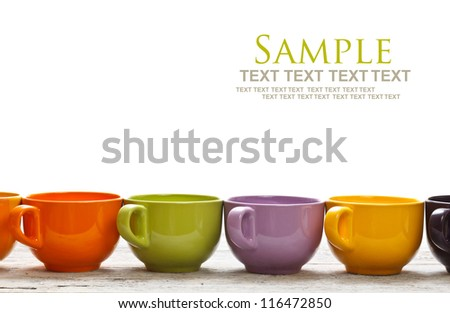 Row of cups on wooden table - stock photo