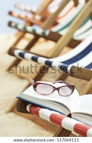 Row of deck chairs on beach book with sunglasses in foreground