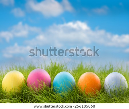 Row of decorated easter eggs in grass on blue sky background - stock photo
