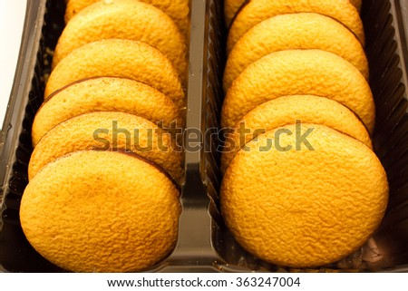 Row of delicious chocolate sponge biscuit chip cookies with jelly in brown box close up, detail - stock photo