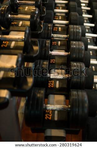 Row of different black dumbbells in sports club