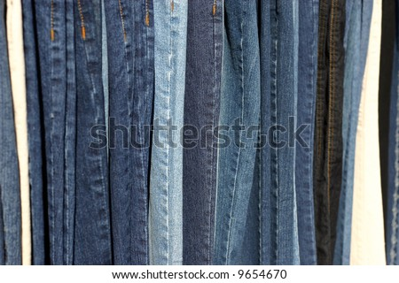 row of different color blue jeans - stock photo