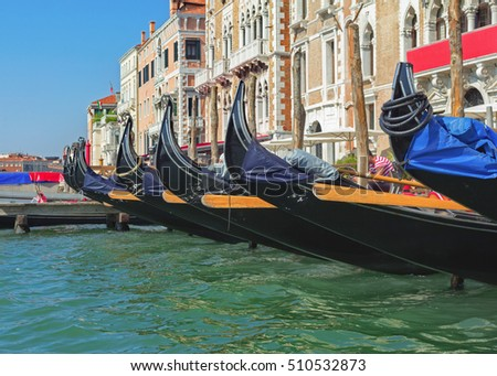 Row of docked venetian gondolas. Gondolas are very popular sort of entertainment in Venice, Italy