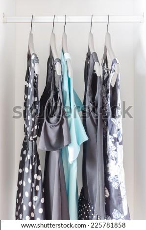row of dress hanging on coat hanger in white wardrobe - stock photo