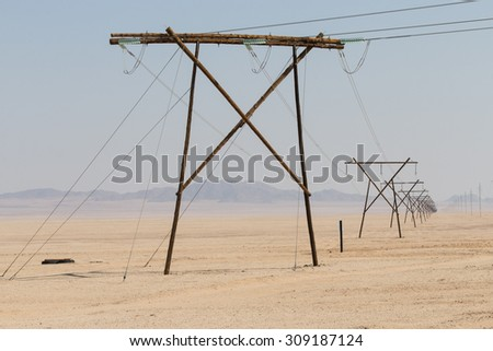 row of electricity pylons in the Namib desert, Namibia, Africa - stock photo