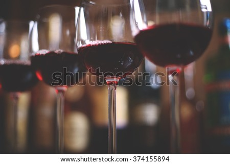 Row of elegant wine glasses with red wine on the bar on the background of a row of alcohol bottles. - stock photo