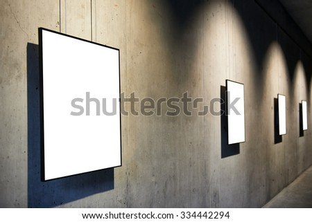 Row of empty black frames on concrete wall in the gallery isolated on white - stock photo