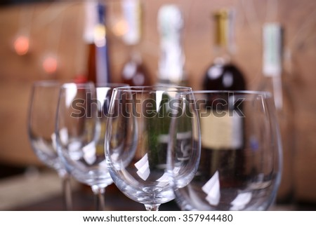 Row of empty wine glasses on the bar in the background bottles with alcohol - stock photo