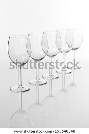 Row of empty wineglasses, with reflection. - stock photo