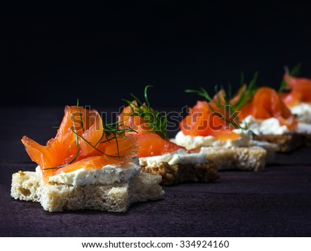 Row of festive canapes in star shape with smoked salmon for Christmas or New Year on a dark wooden background, selected focus, narrow depth of field - stock photo
