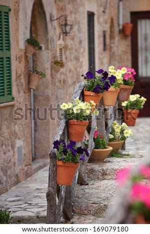 Row of flowerpots lining a street in front of an old stone house - stock photo