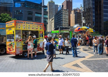 Row of food and drink carts at entrance of Central Park with tourists walking by - July 10, 2015, Columbus Circle, New York City, NY, USA