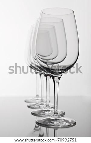 row of four empty wine glasses with a reflection - stock photo