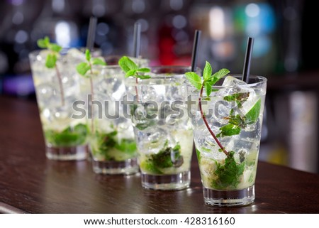 Row of four Mojito cocktails on a bar counter in a club