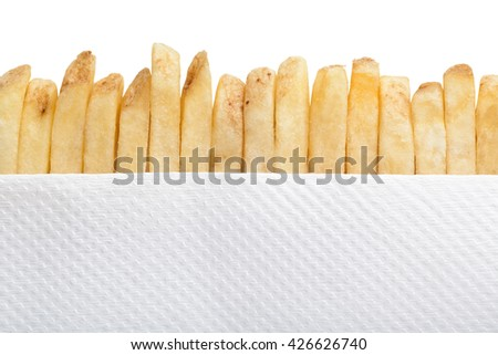 Row of french fries and paper napkin - stock photo
