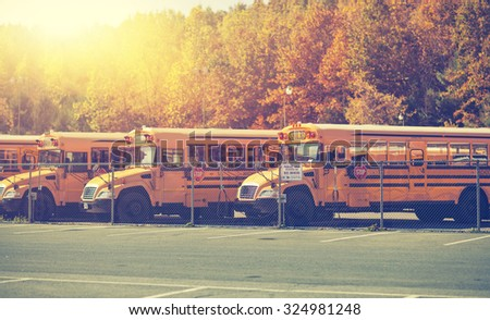 Row of generic school buses during the fall with all identifying markings removed. - stock photo