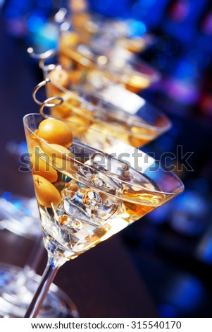 Row of glasses of famous cocktail Martini, shot at a bar with shallow depth of field  Ingredients: 55 ml gin 15 ml dry vermouth olives to garnish - stock photo