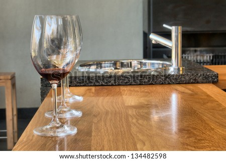 Row of glasses on wine-tasting table. Shot in Winelands near Stellenbosch, Western Cape, South Africa. - stock photo