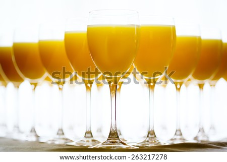 Row of Glasses with Fresh Orange Juice. Catering background. Selective focus, shallow DOF. - stock photo
