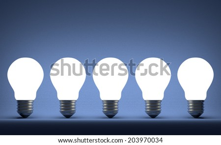 Row of glowing tungsten light bulbs on blue textured background - stock photo