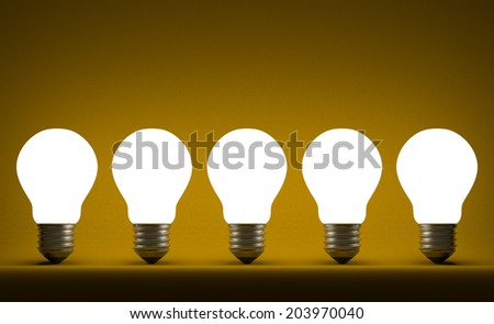 Row of glowing tungsten light bulbs on yellow textured background - stock photo