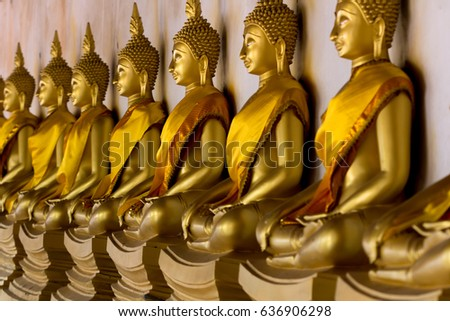 Row of Golden Buddha statues sitting pose in Thailand. selective focus, shallow depth of field, perspective concept.