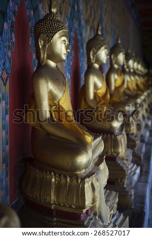 Row of golden seated buddhas in a Buddhist temple in Bangkok Thailand