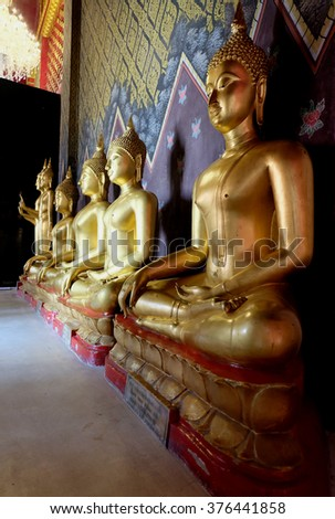 Row of golden seated buddhas in front of decorative wall in a Buddhist temple in  Phitsanulok Thailand - stock photo