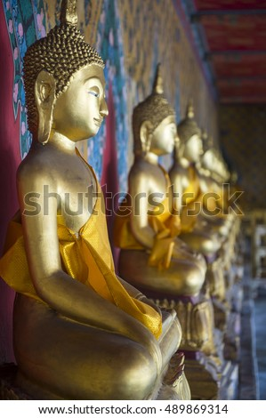 Row of golden seated buddhas wearing yellow sash in front of decorative wall in a Buddhist temple in Bangkok Thailand