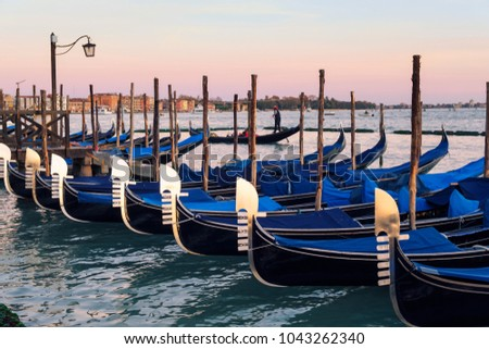 Row of gondolas parked on city pier on Grand Canal in Venice, Italy-Europe